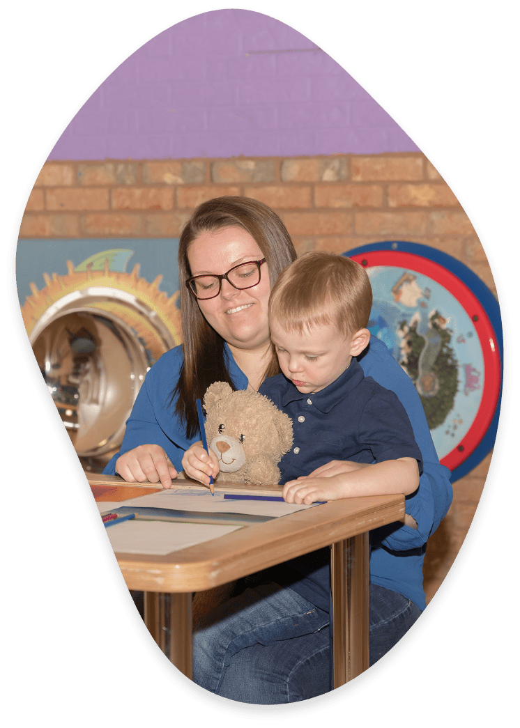 Young boy colouring with teacher